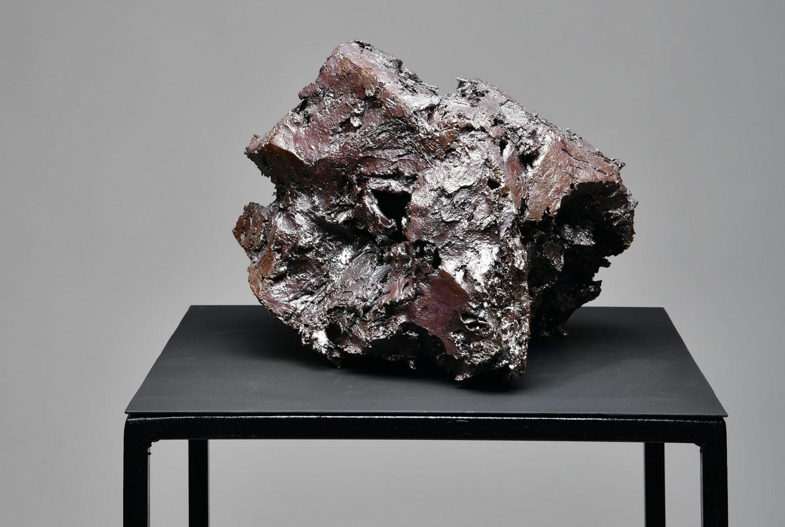 Werk aus dunklem Porzellan von Paul Simon Heyduck auf einem schwarzen Tisch