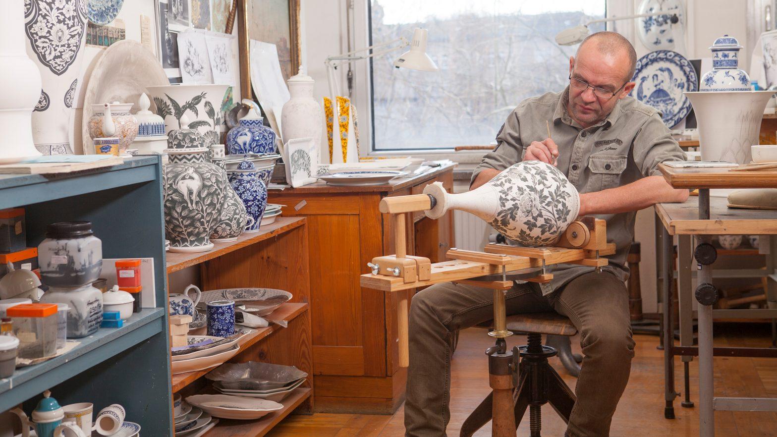 Ein Handwerker bemalt eine Vase in einem Atelier der Staatlichen Porzellan-Manufaktur Meissen
